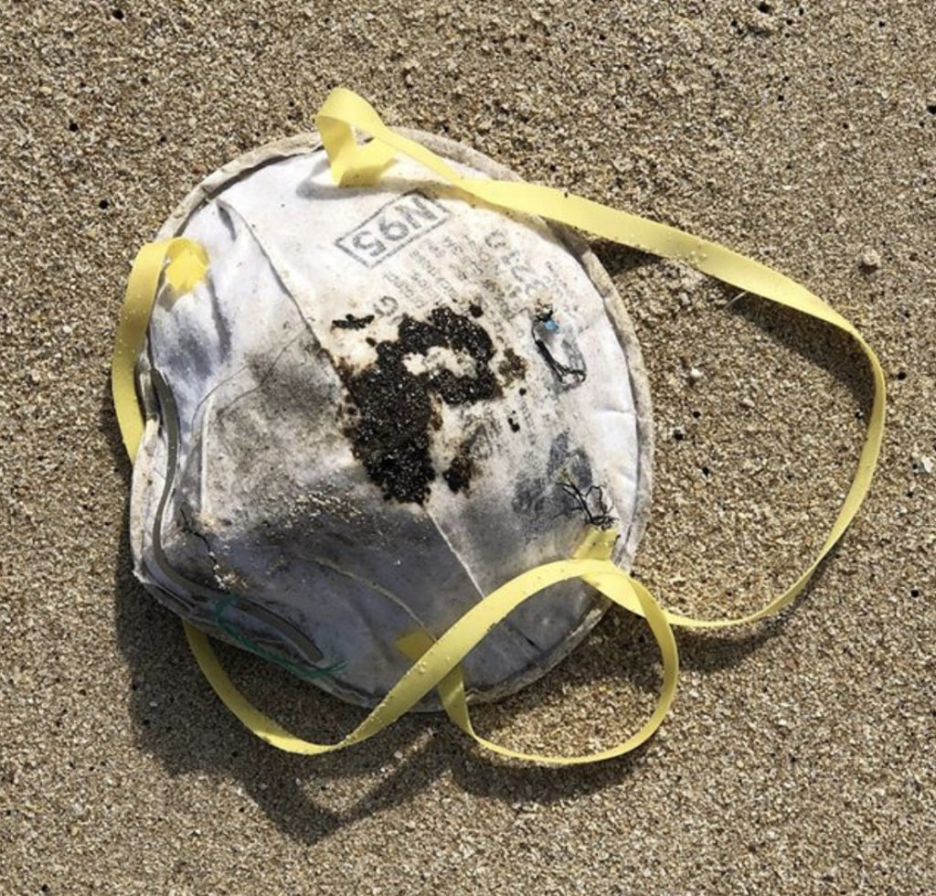 Image shows a discarded face mask on the beach along with other debris.